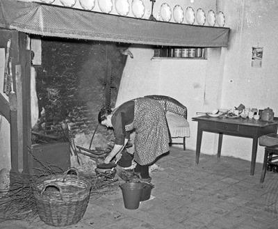 Foto gemaakt in 1955. Volgens de Heemkundekring 'Ledevaert' in Chaam, die dit in 2013 heeft uitgezocht, is dit Sjoke Jansen in haar boerderij aan de Grazenseweg in Strijbeek. Anno 2013 woont in deze boerderij volgens de heemkundekring een makelaar.