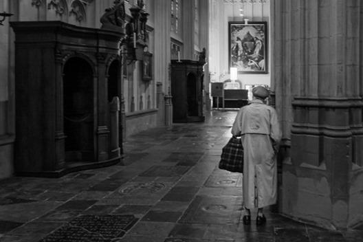 een oude vrouw is voor het gebed in de kathedraal